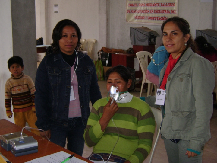 Gianina (l) and Gabriela (r) with asthma patient receiving nebulizer treatment