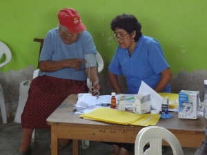Promotora Elva (r) visiting with a patient in the clinic